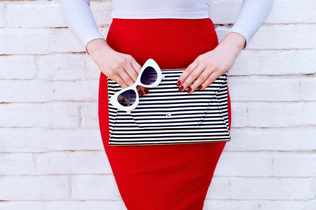A woman in a white top and red pencil skirt holding a black and white striped clutch- an image I would see as inspiration and make me look for more clothes!